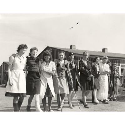 Lazarettpatientinnen werden auf einen Spaziergang geführt. Viele der Frauen leiden noch an Kriegsverletzungen. 7. Mai 1945